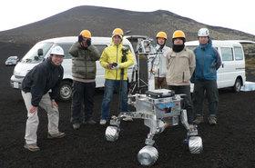 伊豆大島でロボット実証試験大会を主催中。中腰の白ヘルメットが佐伯。ロボットはJAXAチームのもの。